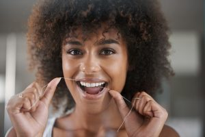 young woman, flossing teeth, woman flossing, woman smiling