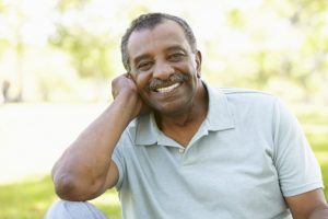 older man smiling with nice teeth after receiving dental implants