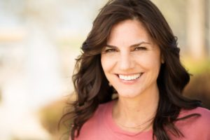 Woman smiling outside after visiting her cosmetic dentist