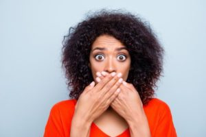 woman with cracked teeth covering her mouth with her hands